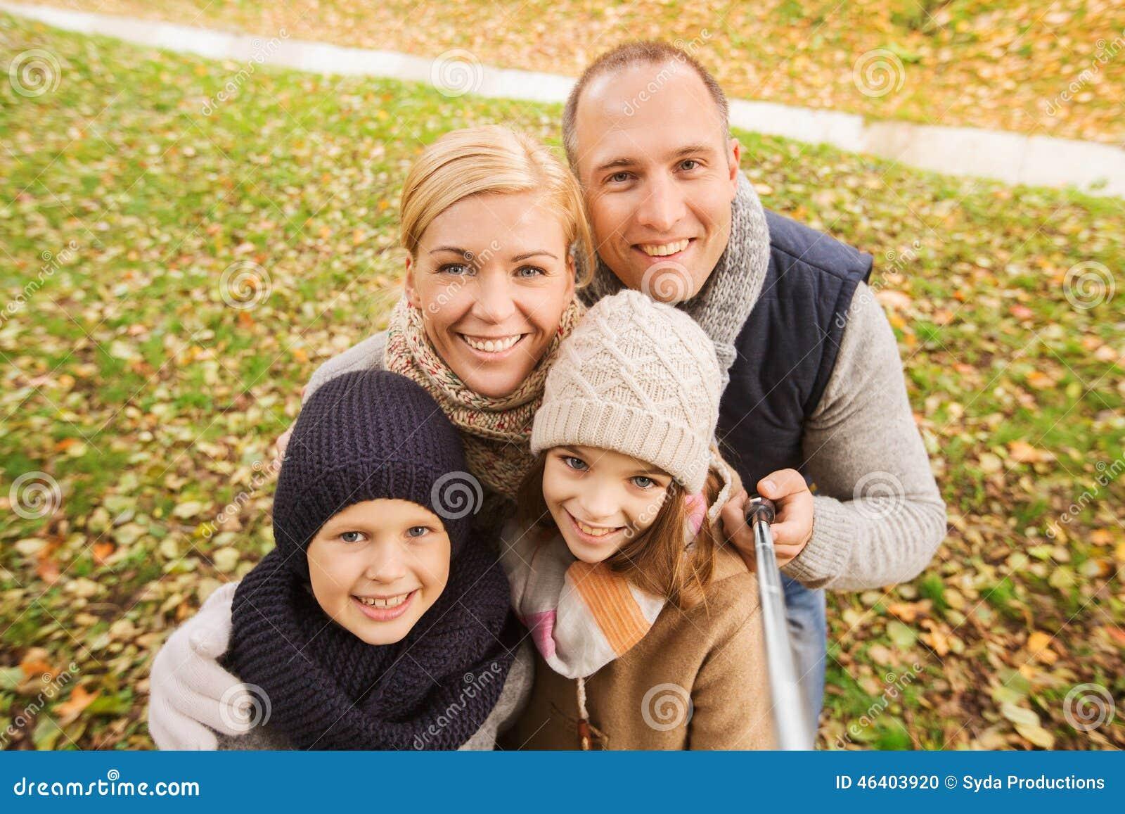 Familia feliz con el palillo del selfie en parque del otoño