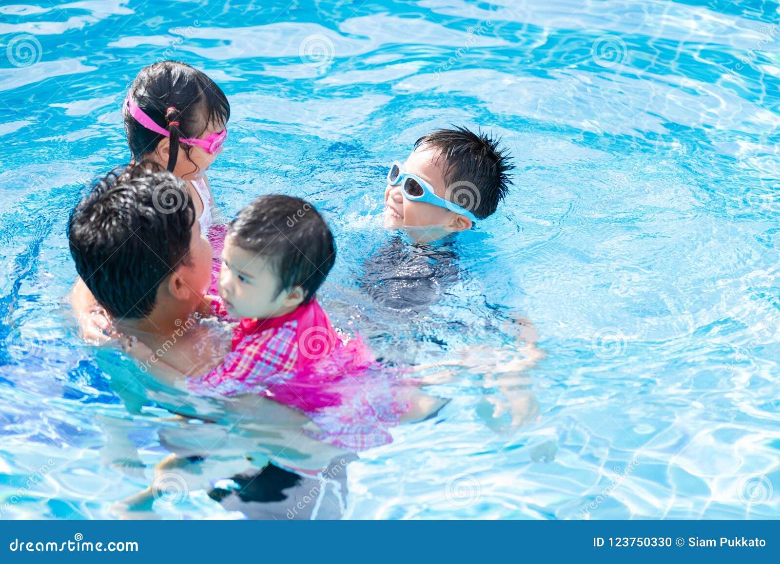 Familia feliz con los niños que se divierten en piscina