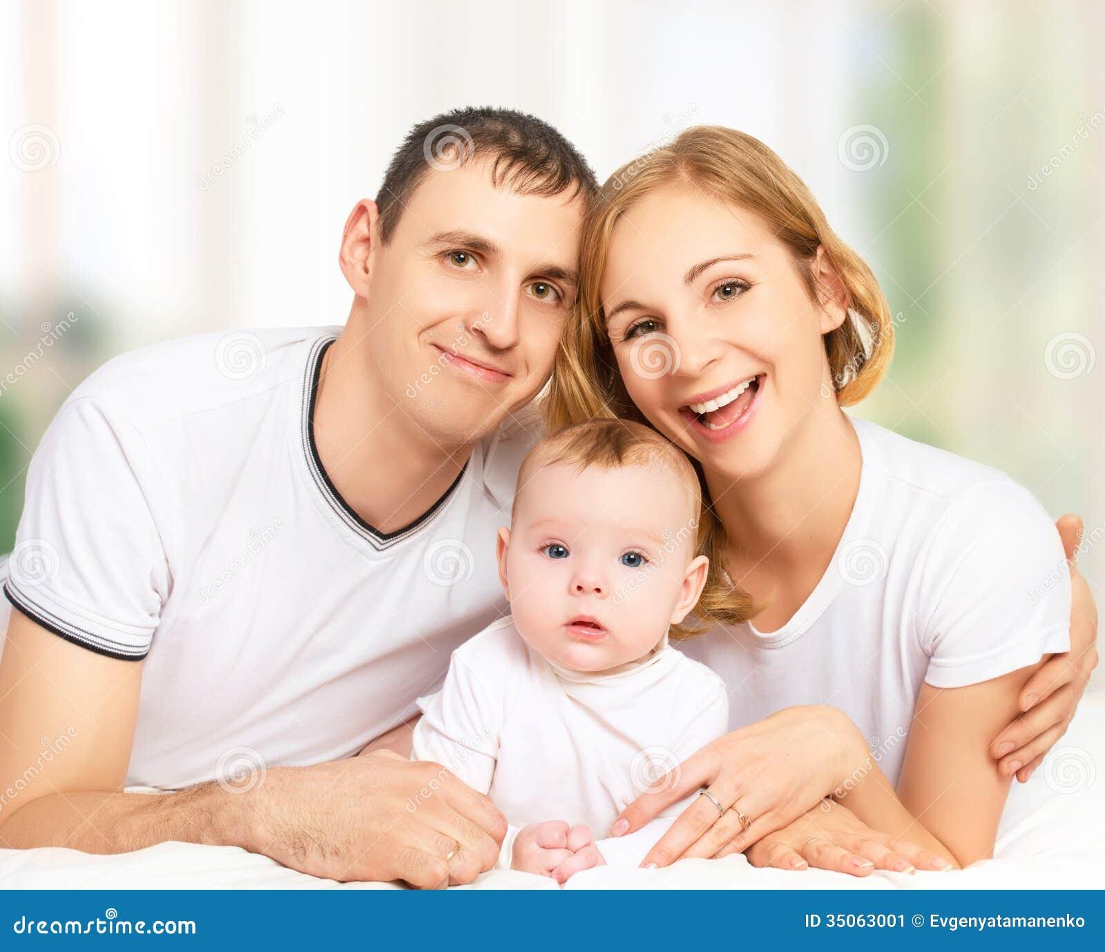 Familia feliz de padre, de madre y de pequeña hija del bebé adentro