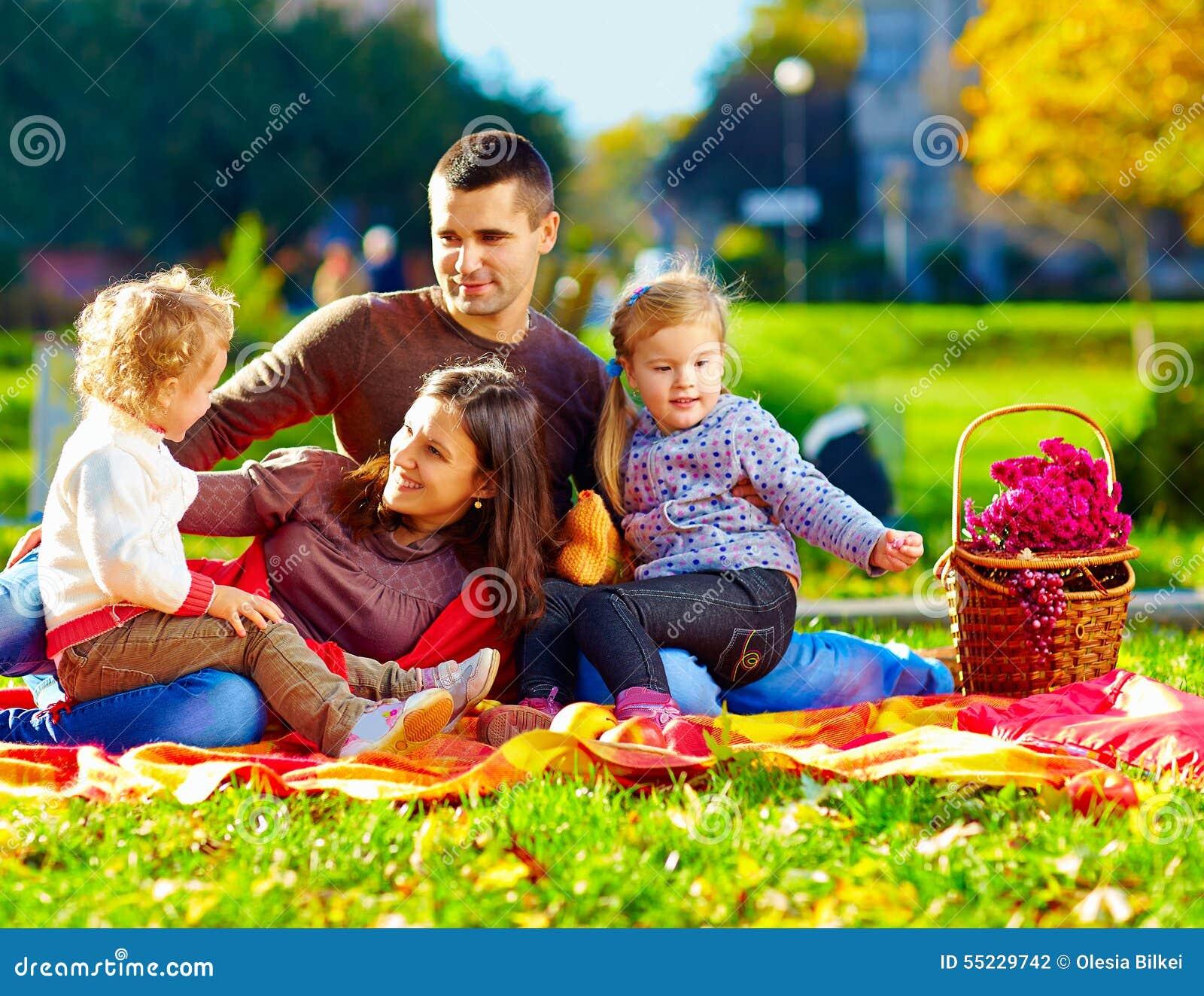 Familia feliz en comida campestre del otoño en parque