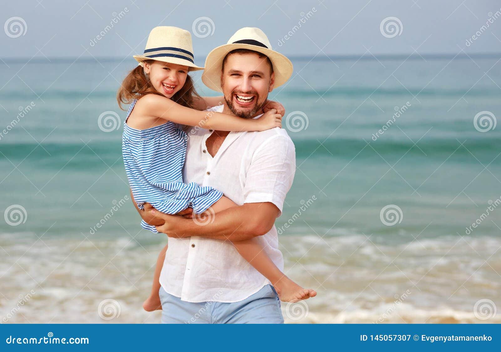 Familia feliz en la playa abrazo de la hija del padre y del ni?o en el mar