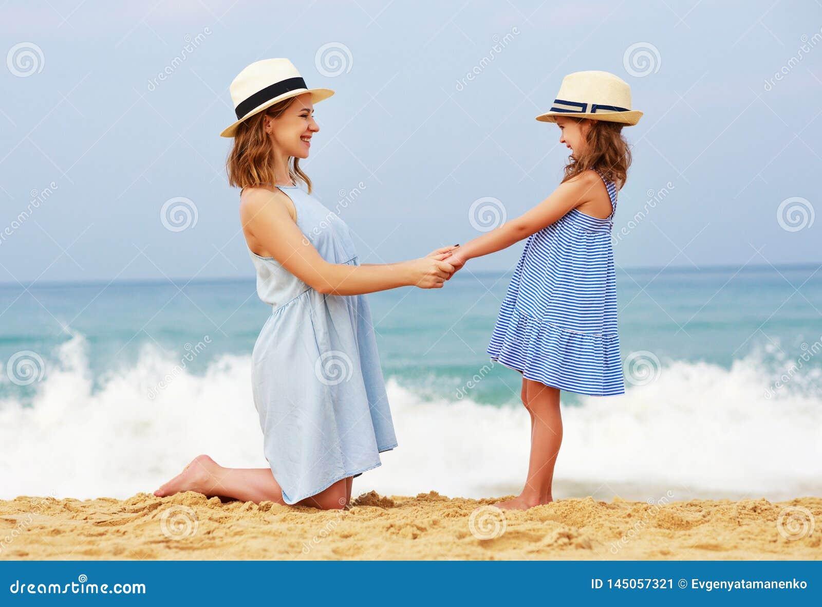 Familia feliz en la playa abrazo de la hija de la madre y del ni?o en el mar