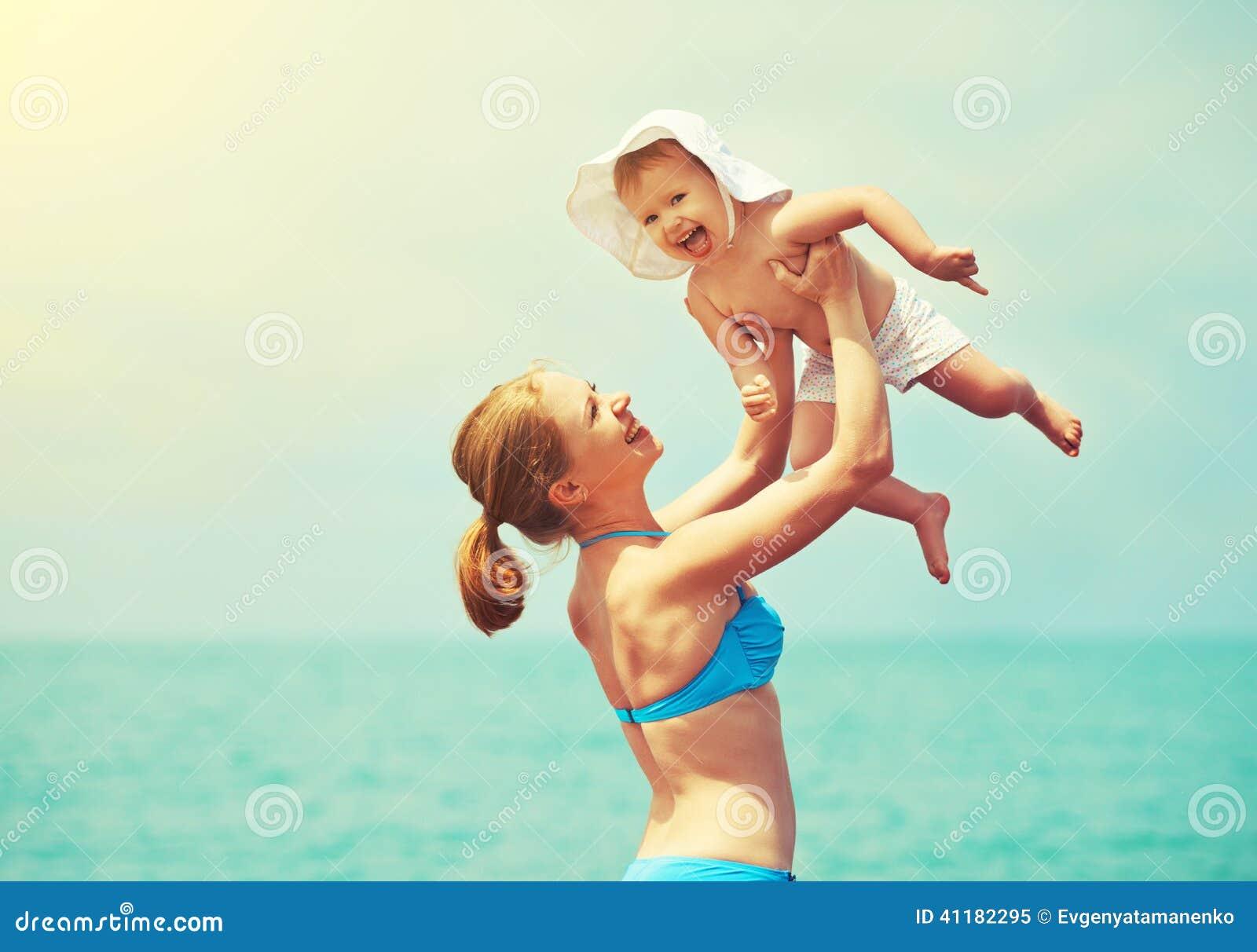 Familia feliz en la playa la madre lanza para arriba la hija del bebé y el pl