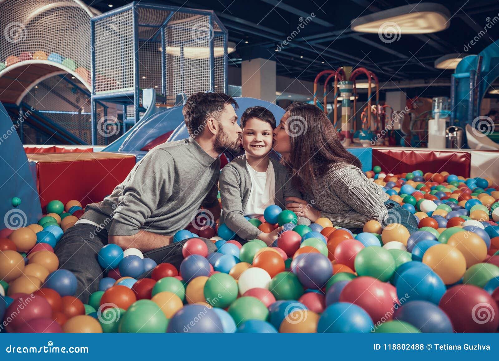 Familia feliz en piscina con las bolas