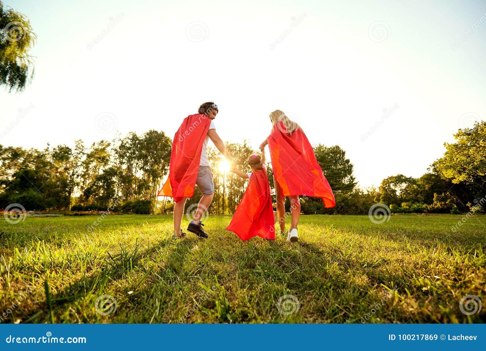 Familia feliz en trajes de super héroes en el parque en la puesta del sol