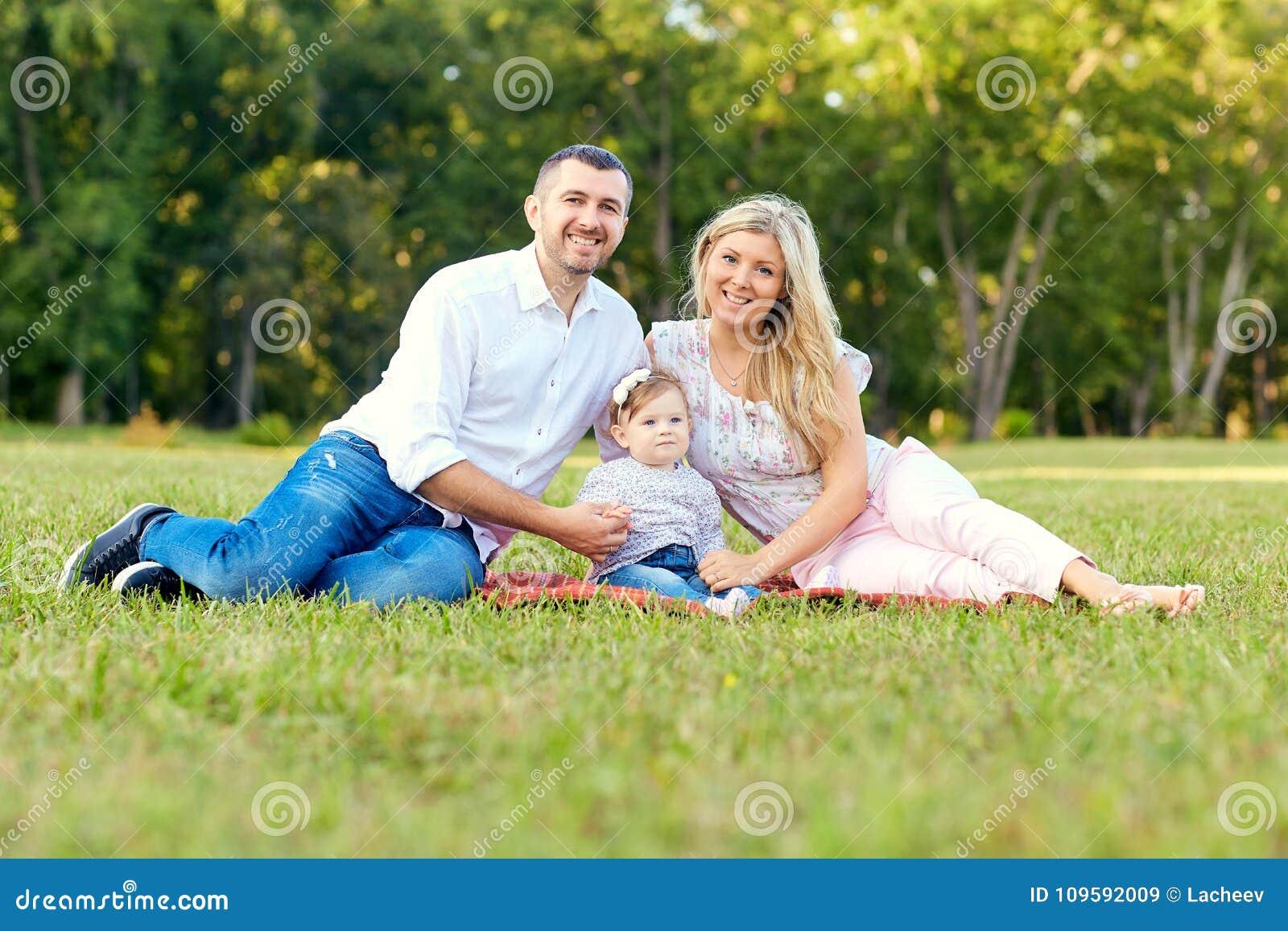 Familia feliz en un parque en otoño del verano Madre, padre y bebé