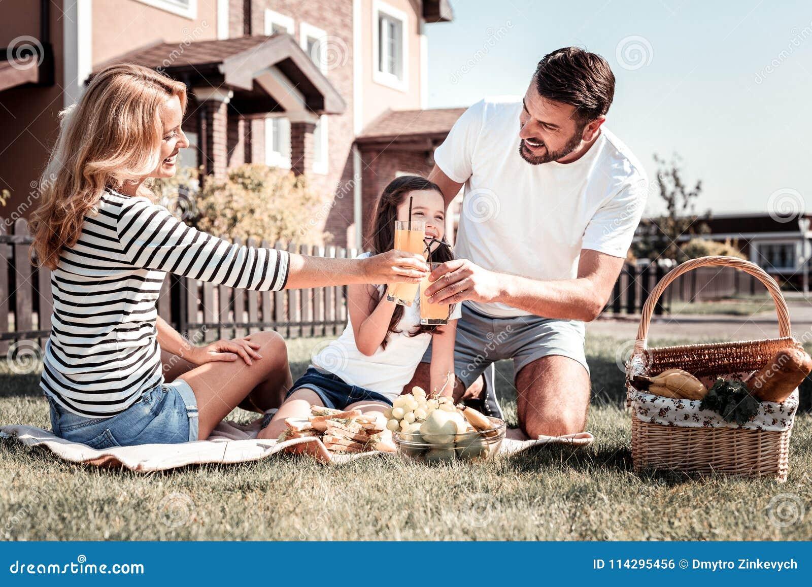 Familia feliz linda que pasa el tiempo junto que tiene una comida campestre