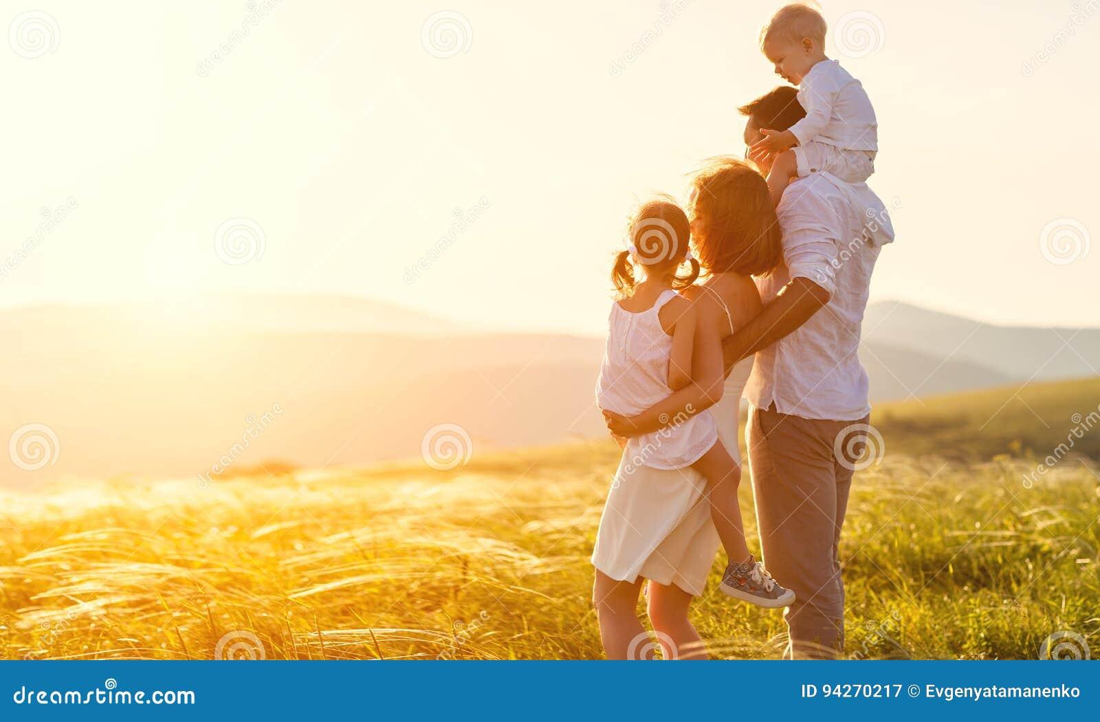 Familia feliz: madre, padre, niños hijo e hija en sunse