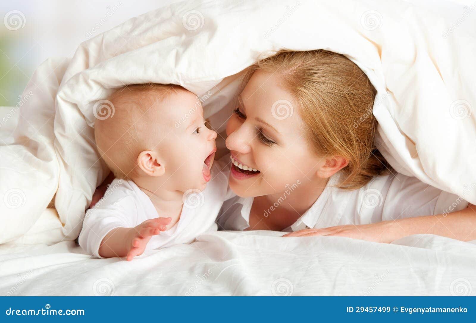 Familia feliz. Madre y bebé que juegan bajo la manta