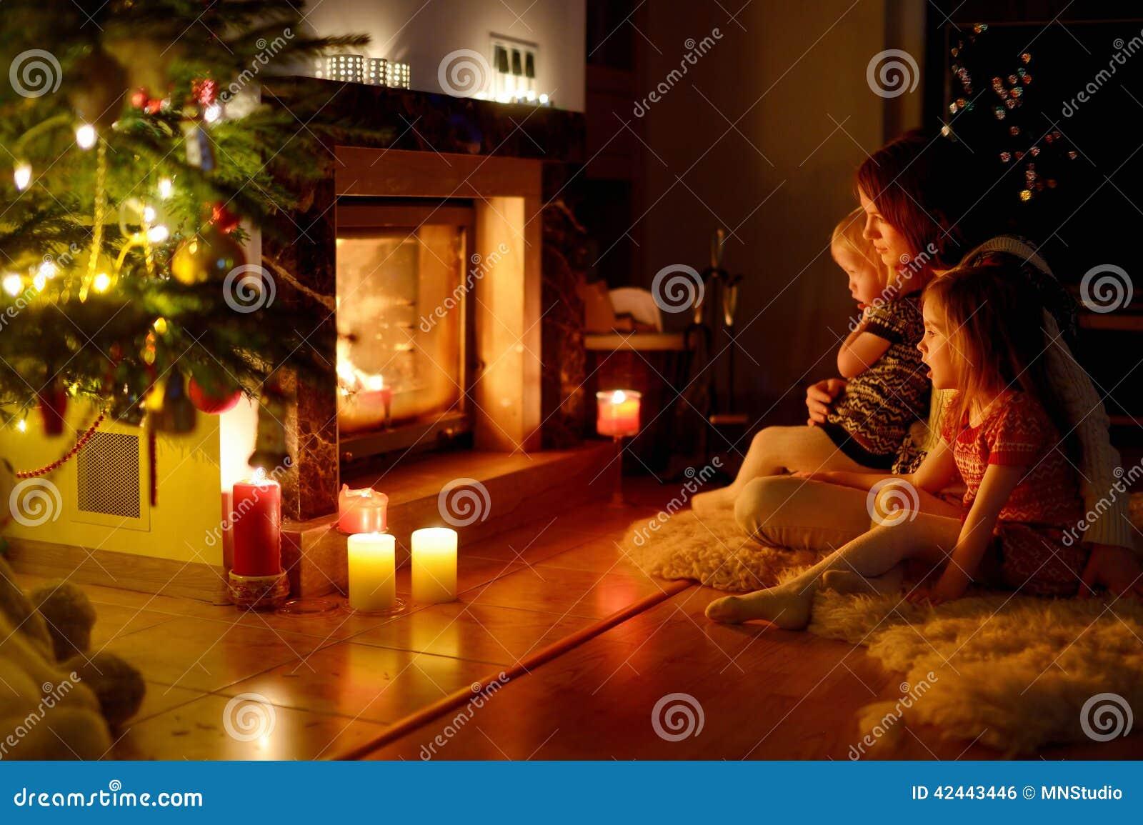 Familia feliz por una chimenea en la Navidad