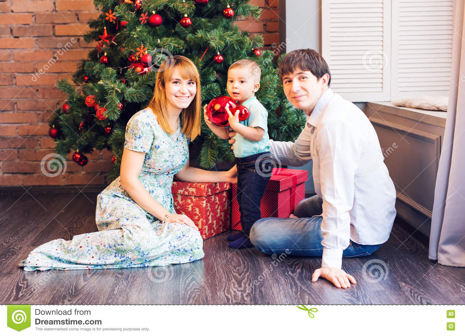Familia feliz que adorna el árbol de navidad junto Padre, madre e hijo Niño lindo cabrito
