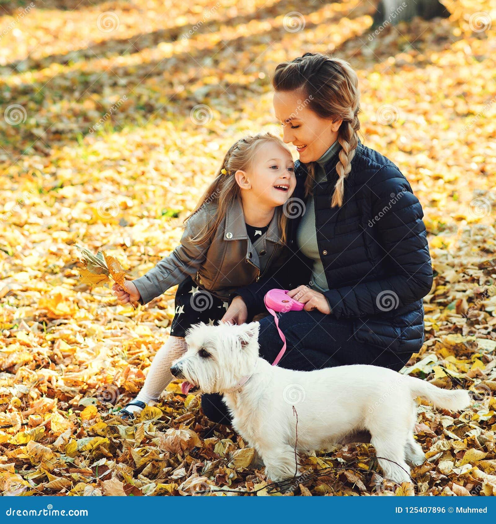 Familia feliz que camina con el perro en parque del otoño Madre e hija jovenes con el perro blanco que se divierte en hojas caida
