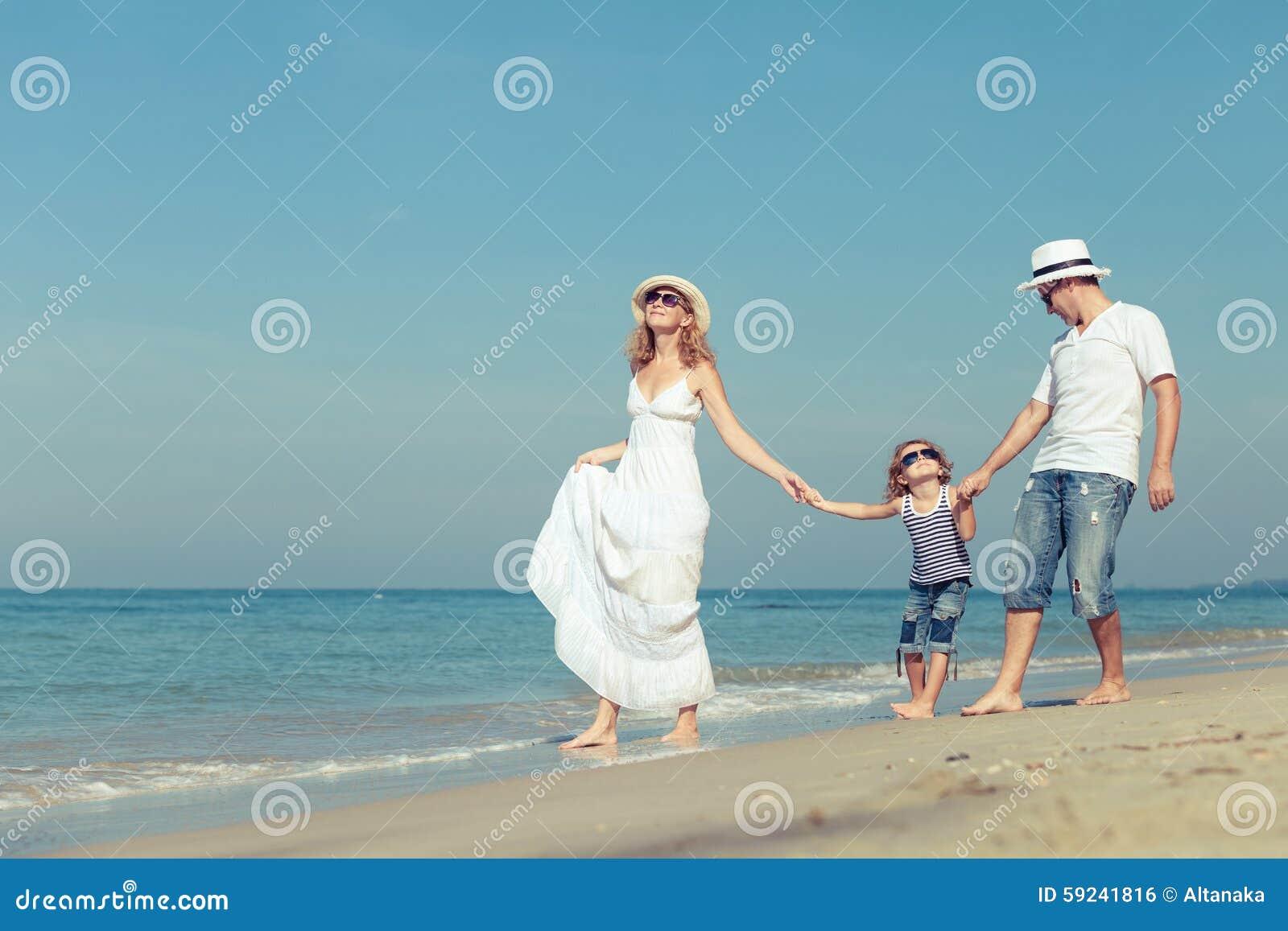 Download Familia Feliz Que Camina En La Playa En El Tiempo Del Día Foto de archivo - Imagen de felicidad, día: 59241816