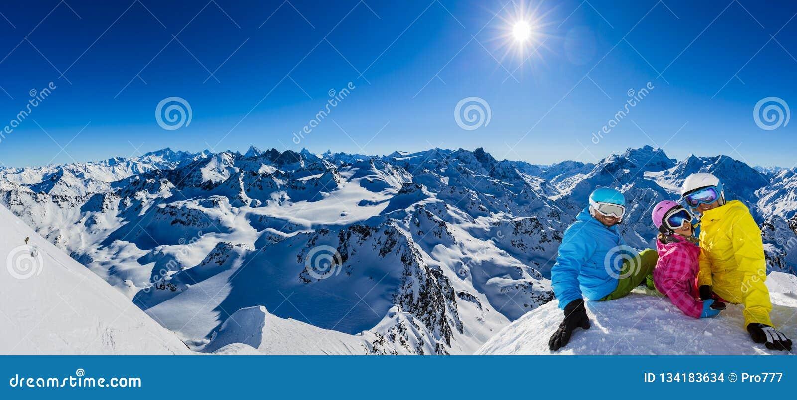 Familia feliz que disfruta de vacaciones del invierno en montañas
