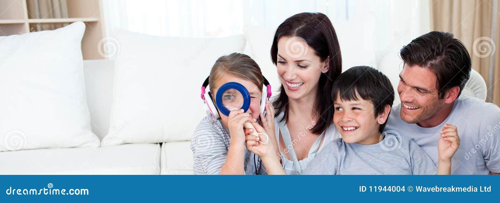Familia feliz que juega con una lupa