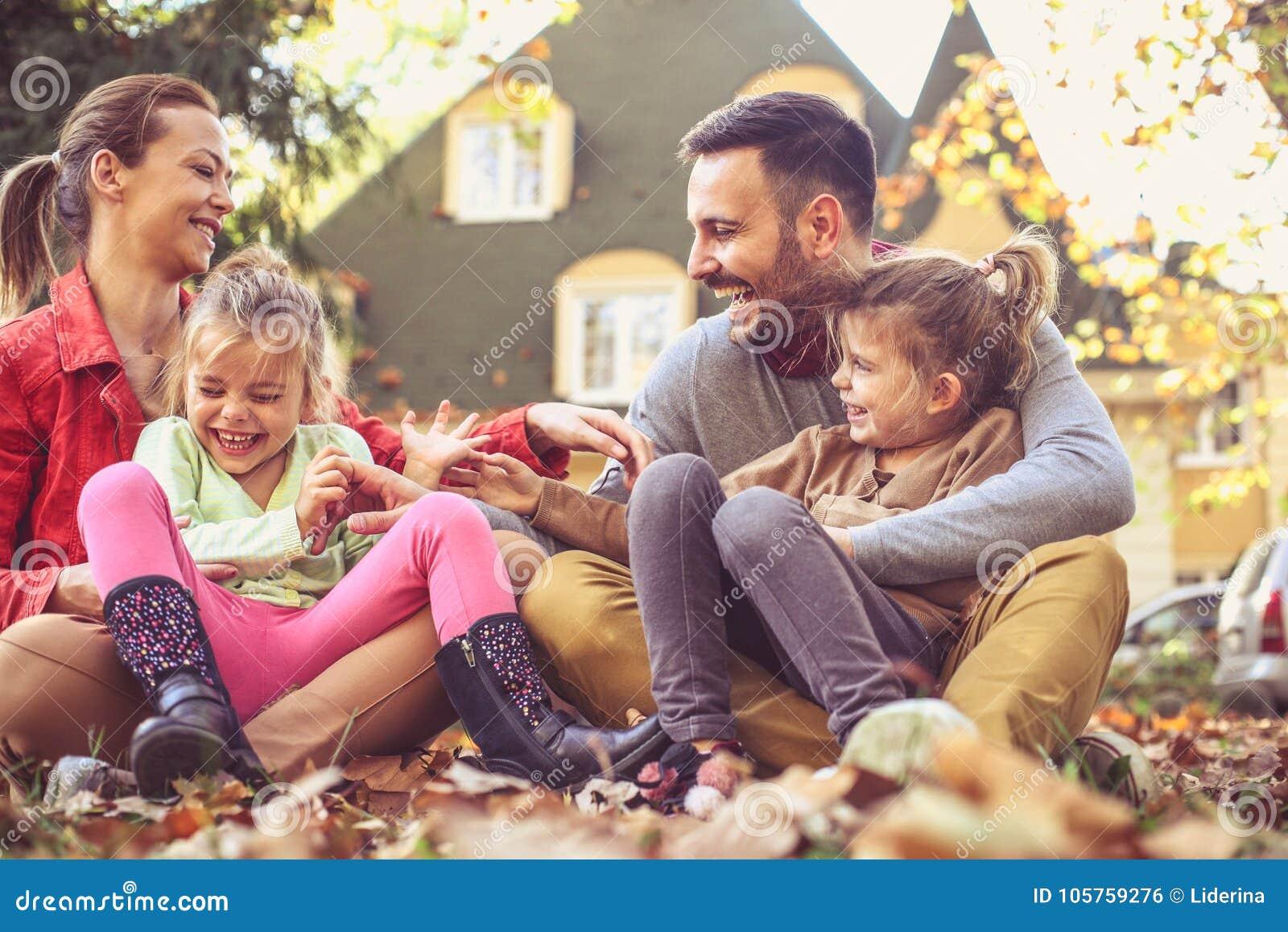 Familia feliz que juega en el patio trasero, estación del otoño