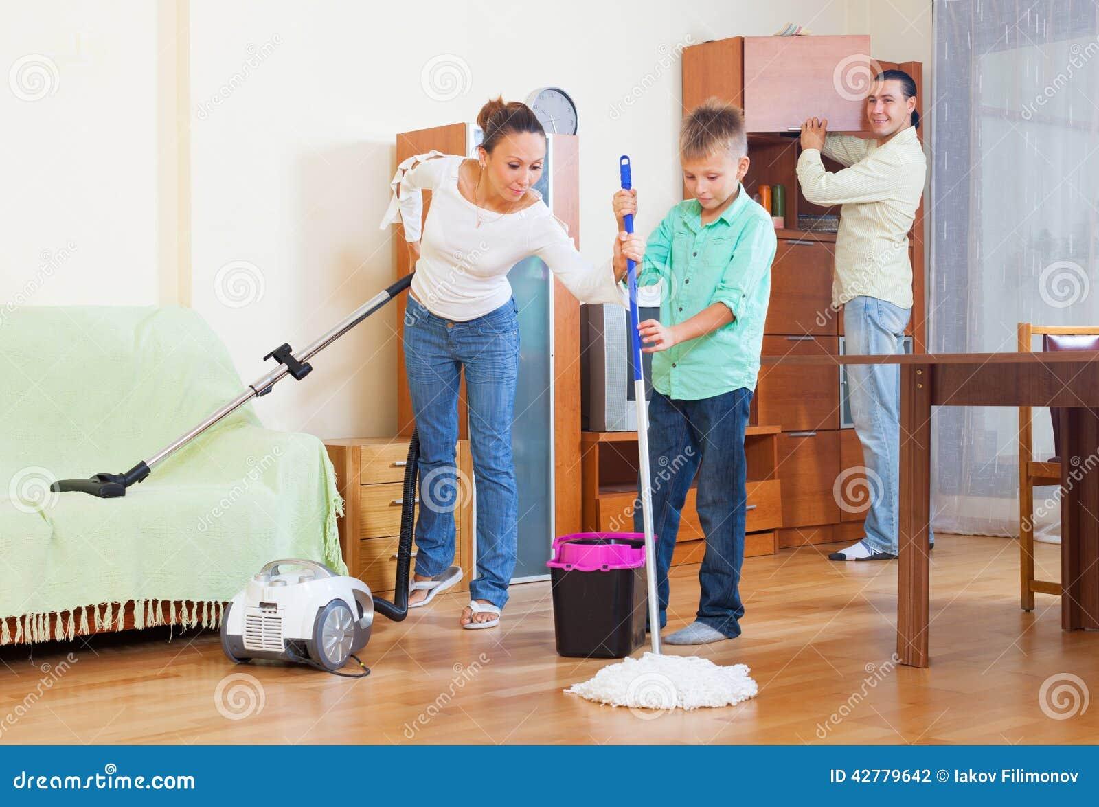 Familia feliz que limpia con la aspiradora en casa foto de - Limpieza en casas ...