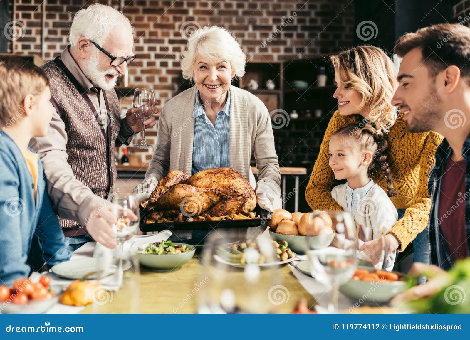Familia feliz que mira el pavo delicioso de la acción de gracias en manos
