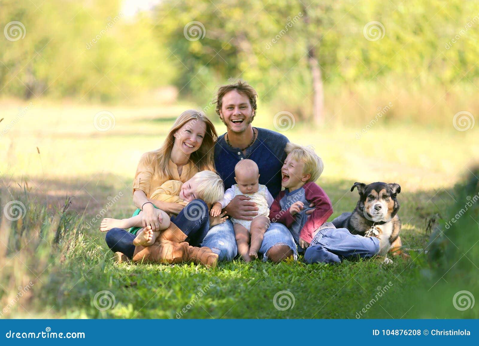 Familia feliz que ríe así como perro afuera