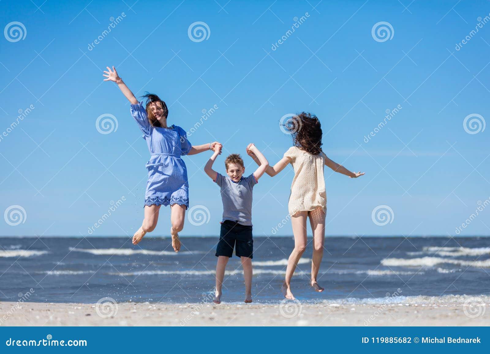 Familia feliz que salta arriba en la costa