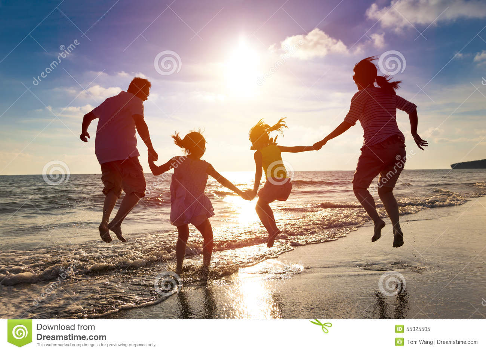 Familia feliz que salta en la playa