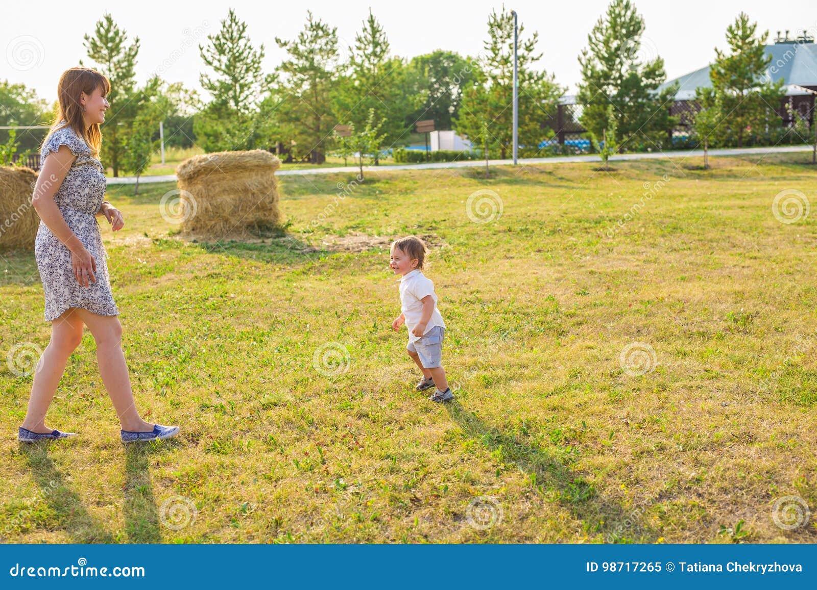 Familia feliz que se divierte bebé y su madre que juegan al aire libre