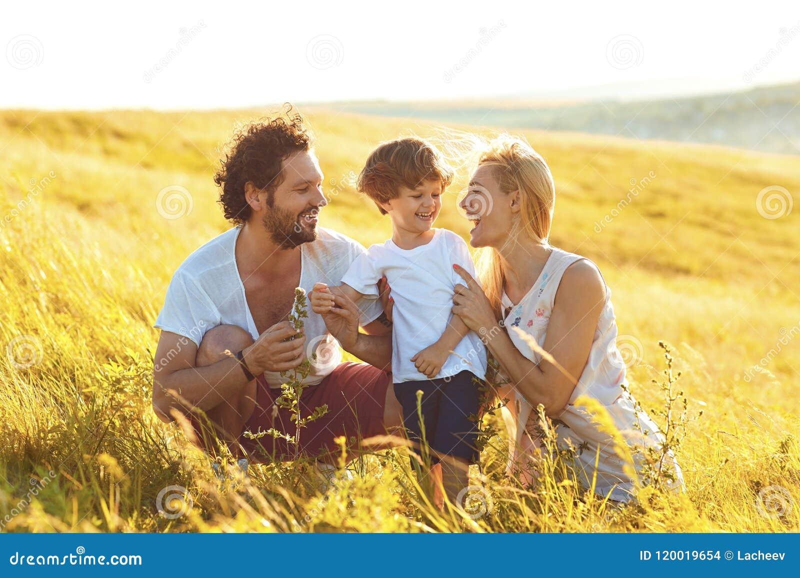 Familia feliz que se divierte que juega en el campo