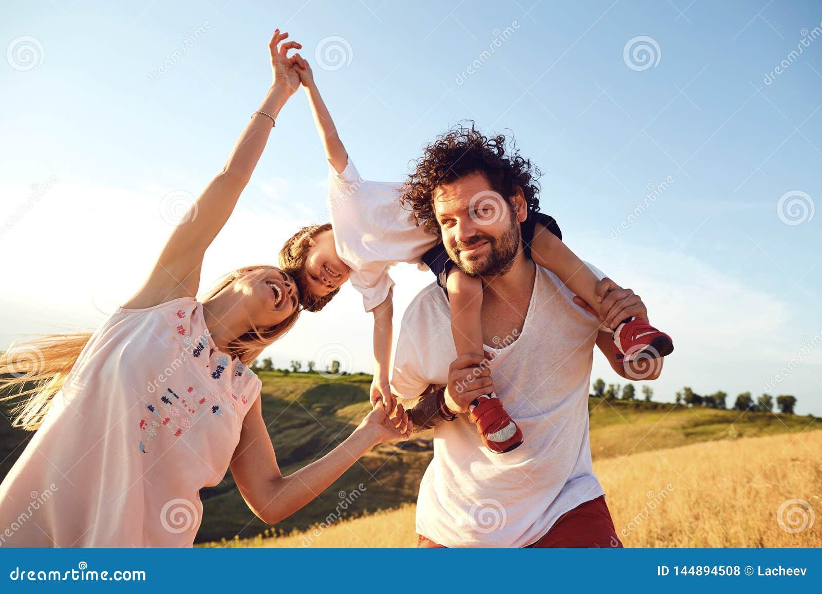 Familia feliz que se divierte que juega en naturaleza