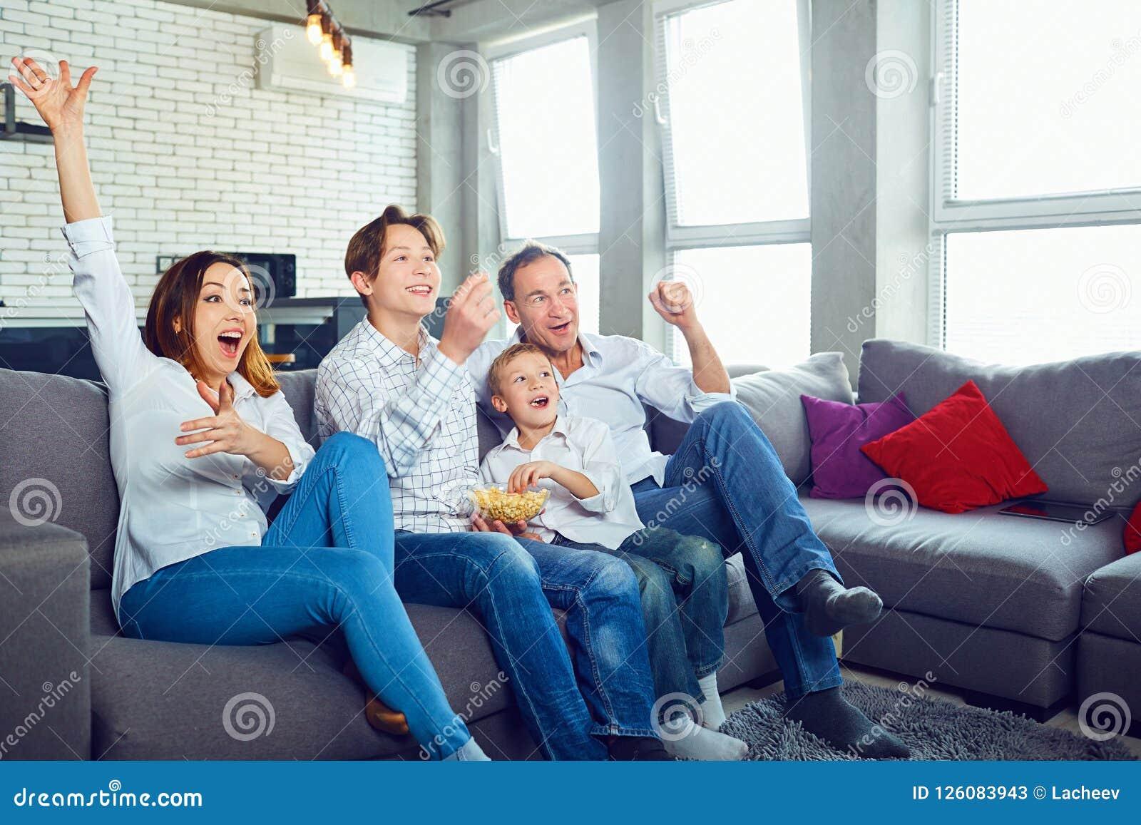 Familia feliz que se divierte que mira la sentada de la TV
