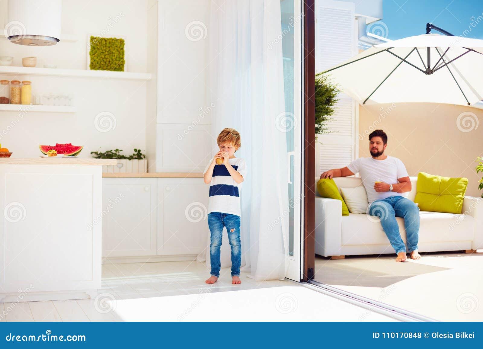 Familia feliz que se relaja en patio del tejado con la cocina del espacio abierto en el día de verano caliente