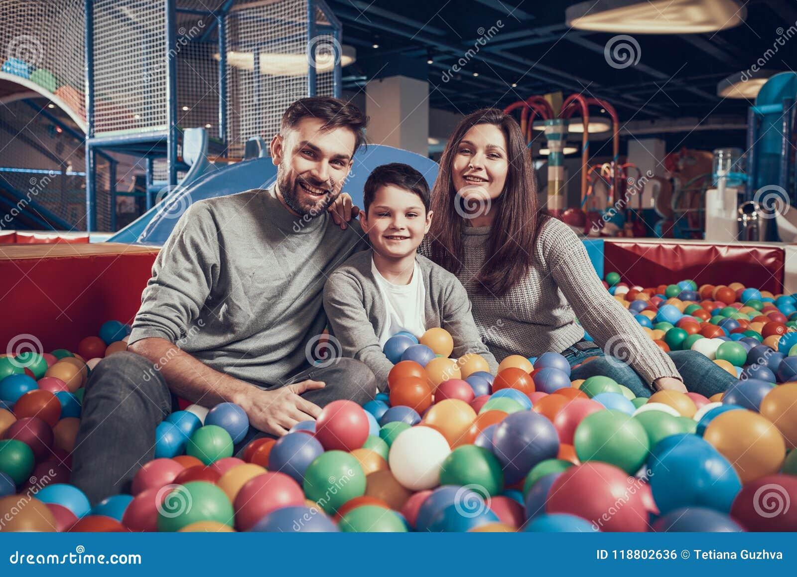 Familia feliz que se sienta en piscina con las bolas