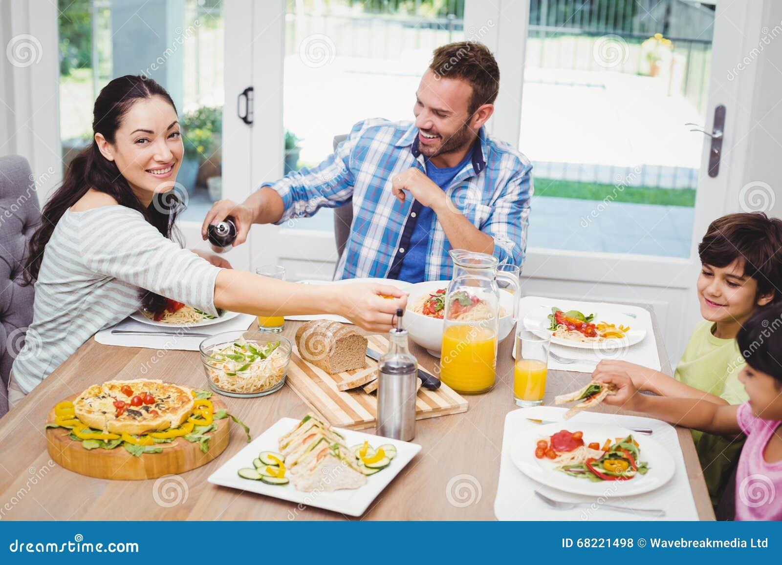 Familia feliz que tiene comida mientras que se sienta en for Comedor que se extiende