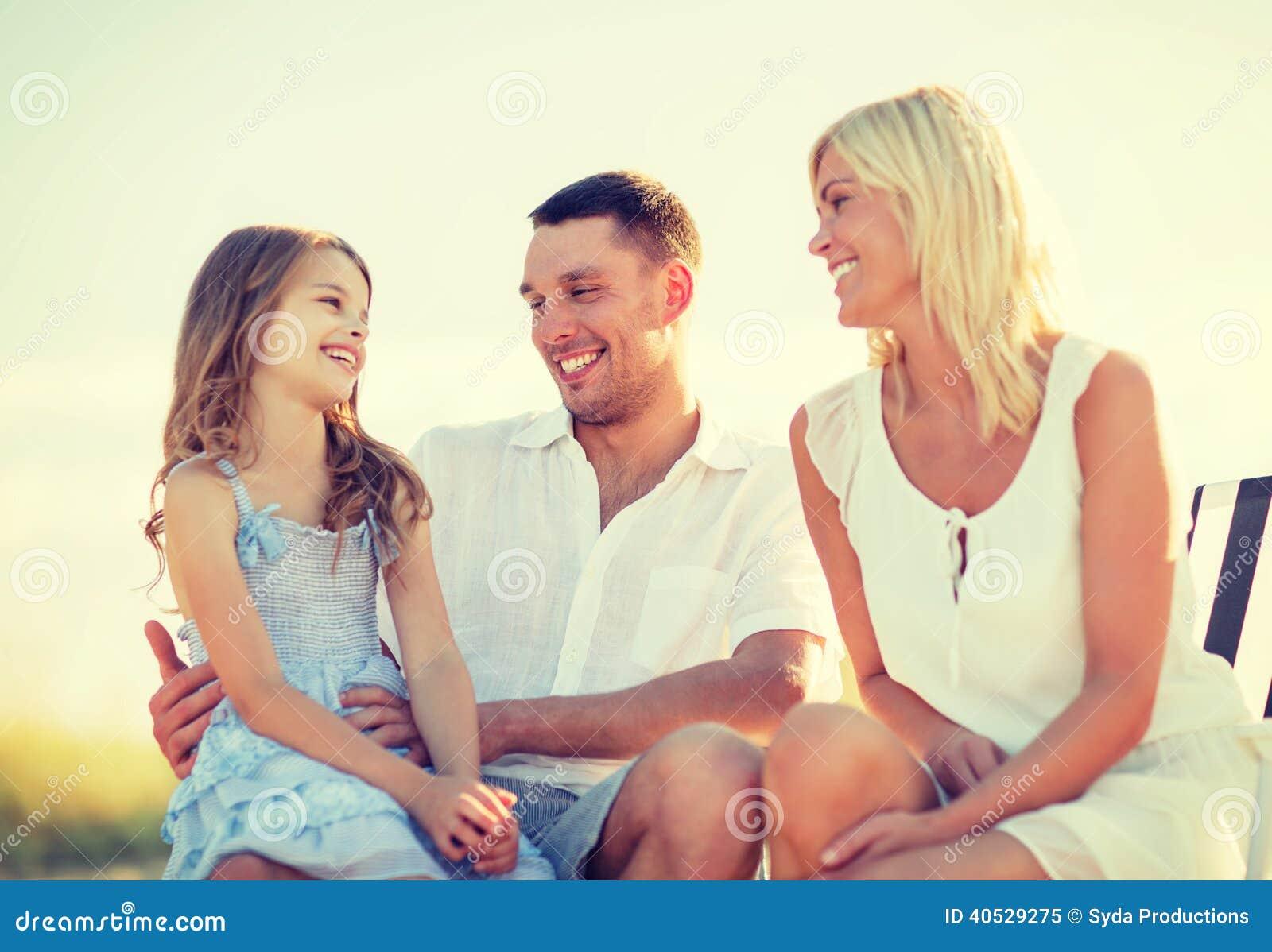 Familia feliz que tiene una comida campestre