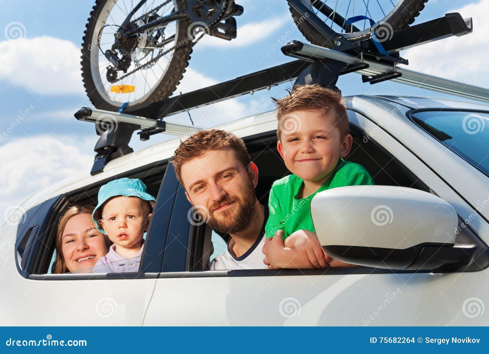 Familia feliz que viaja en coche el vacaciones de verano