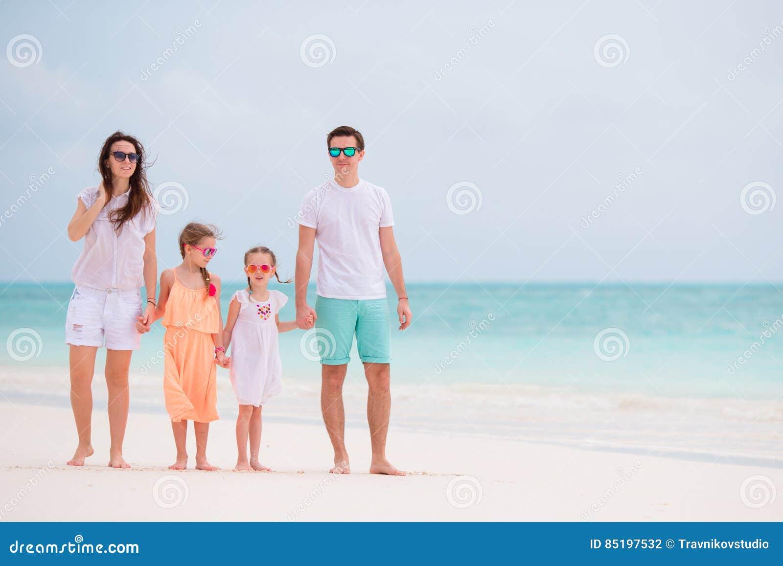 Familia hermosa feliz con los niños que caminan junto en la playa tropical durante vacaciones de verano