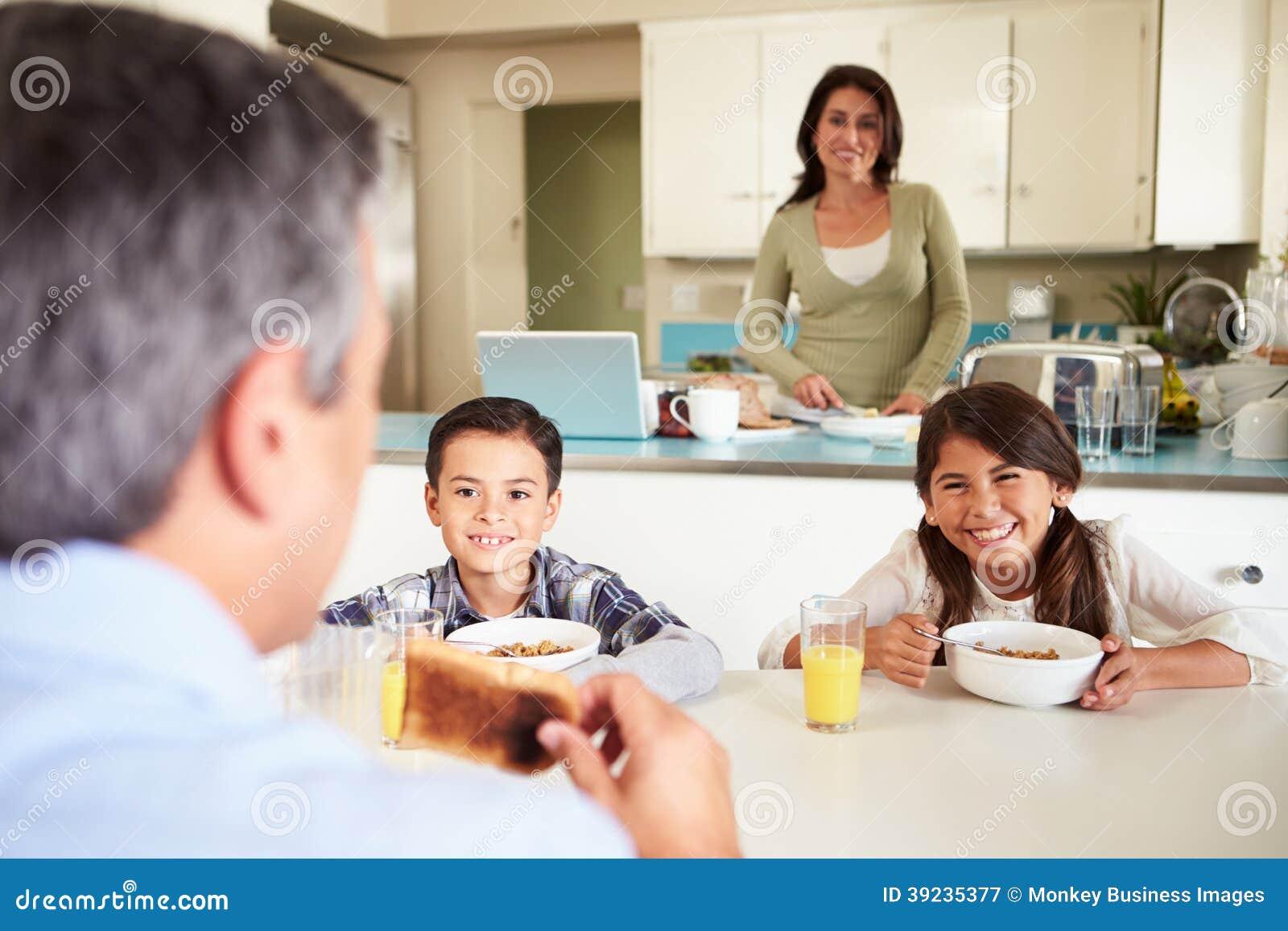 Familia hispánica que come el desayuno en casa junto