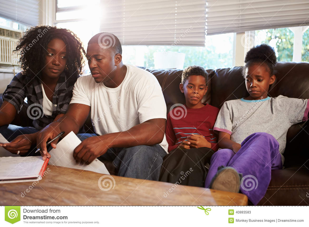 Familia infeliz que se sienta en Sofa Looking At Bills
