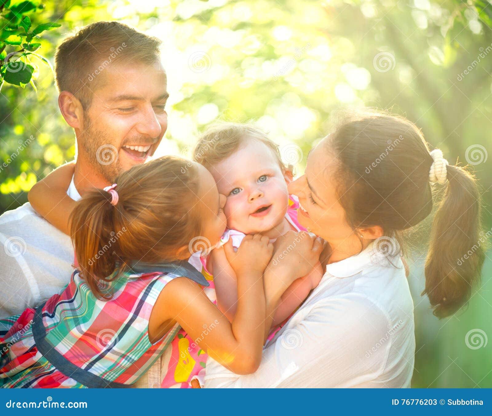 Familia joven alegre feliz que se divierte al aire libre