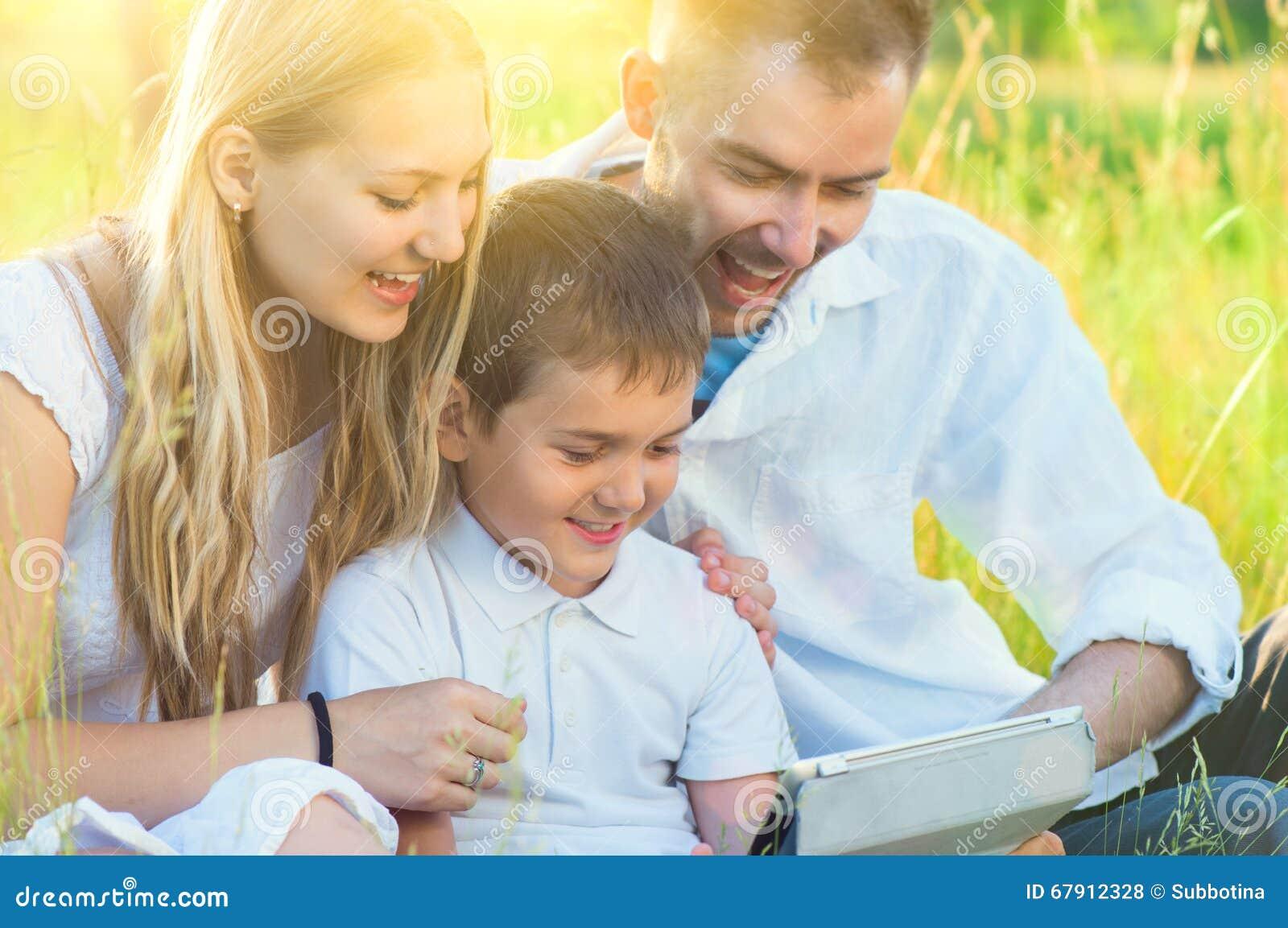 Familia joven con el niño usando la tableta en parque del verano