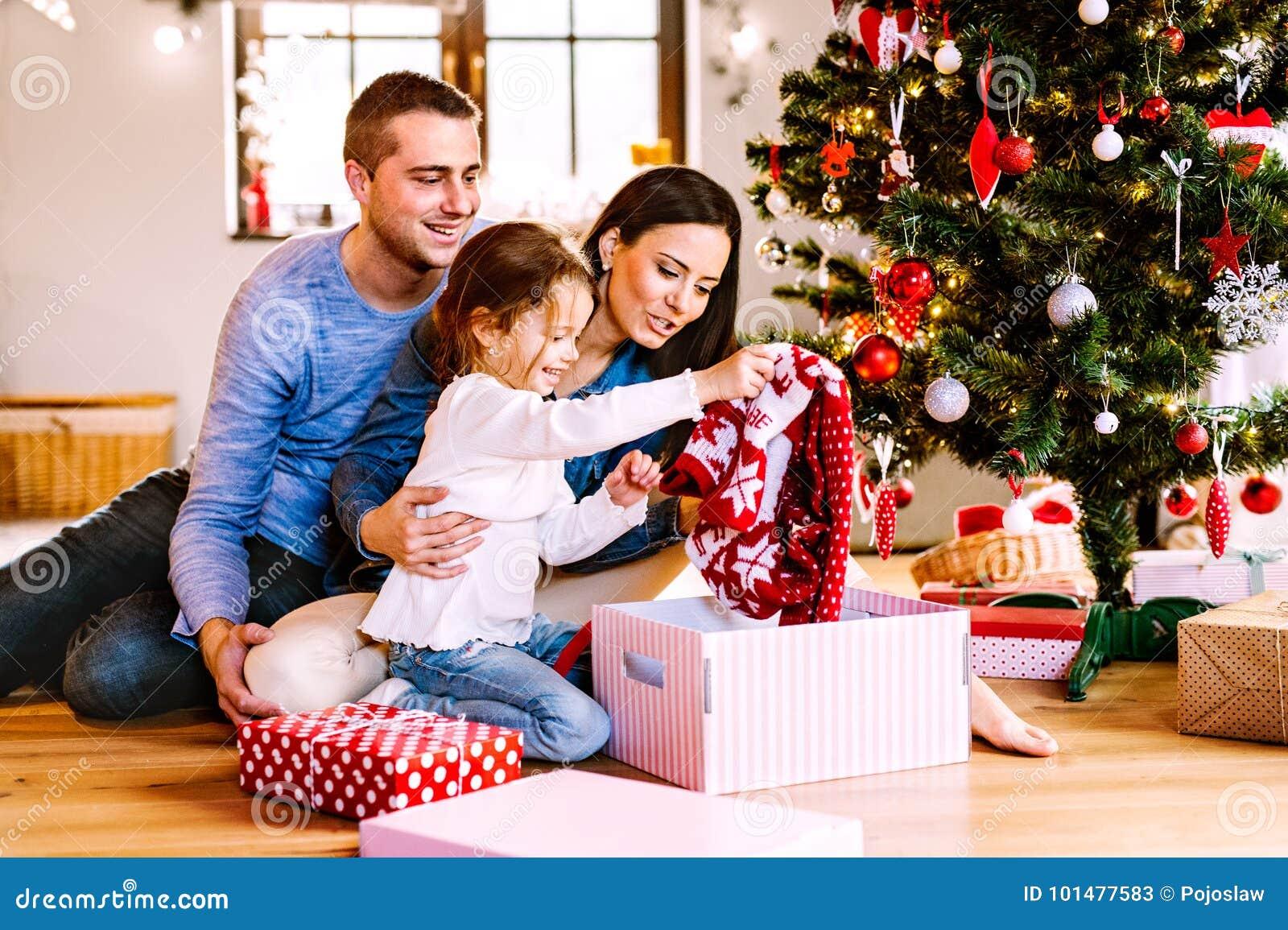 Familia joven con la hija en el árbol de navidad en casa