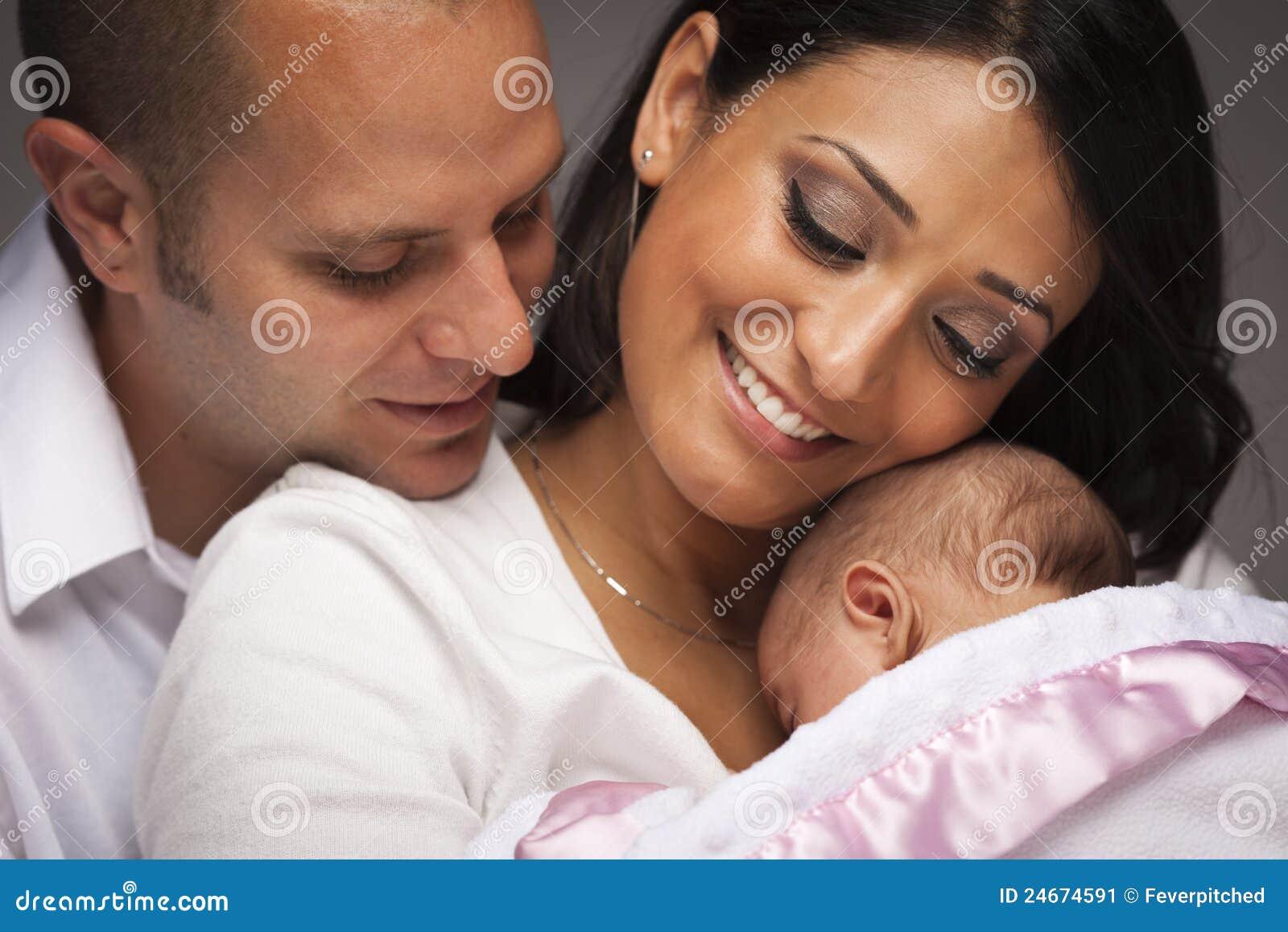 Familia joven de la raza mezclada con el bebé recién nacido