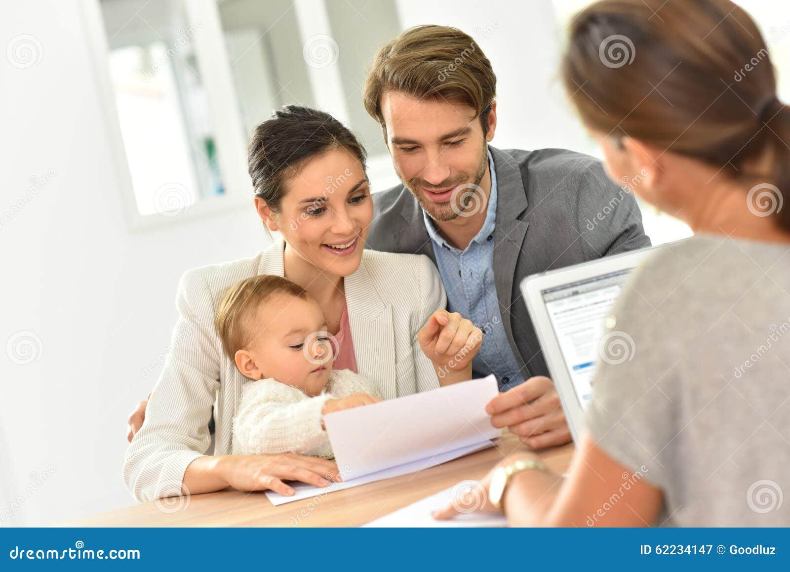 Familia joven en agencia inmobiliaria que compra la nueva casa