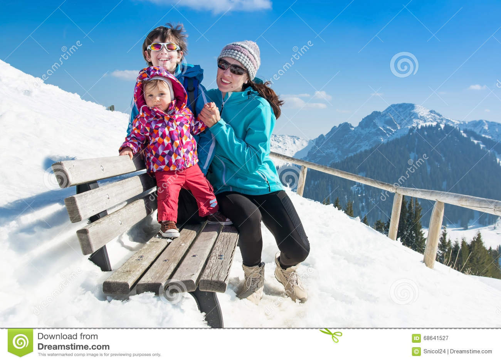 Familia joven feliz en vacaciones del invierno