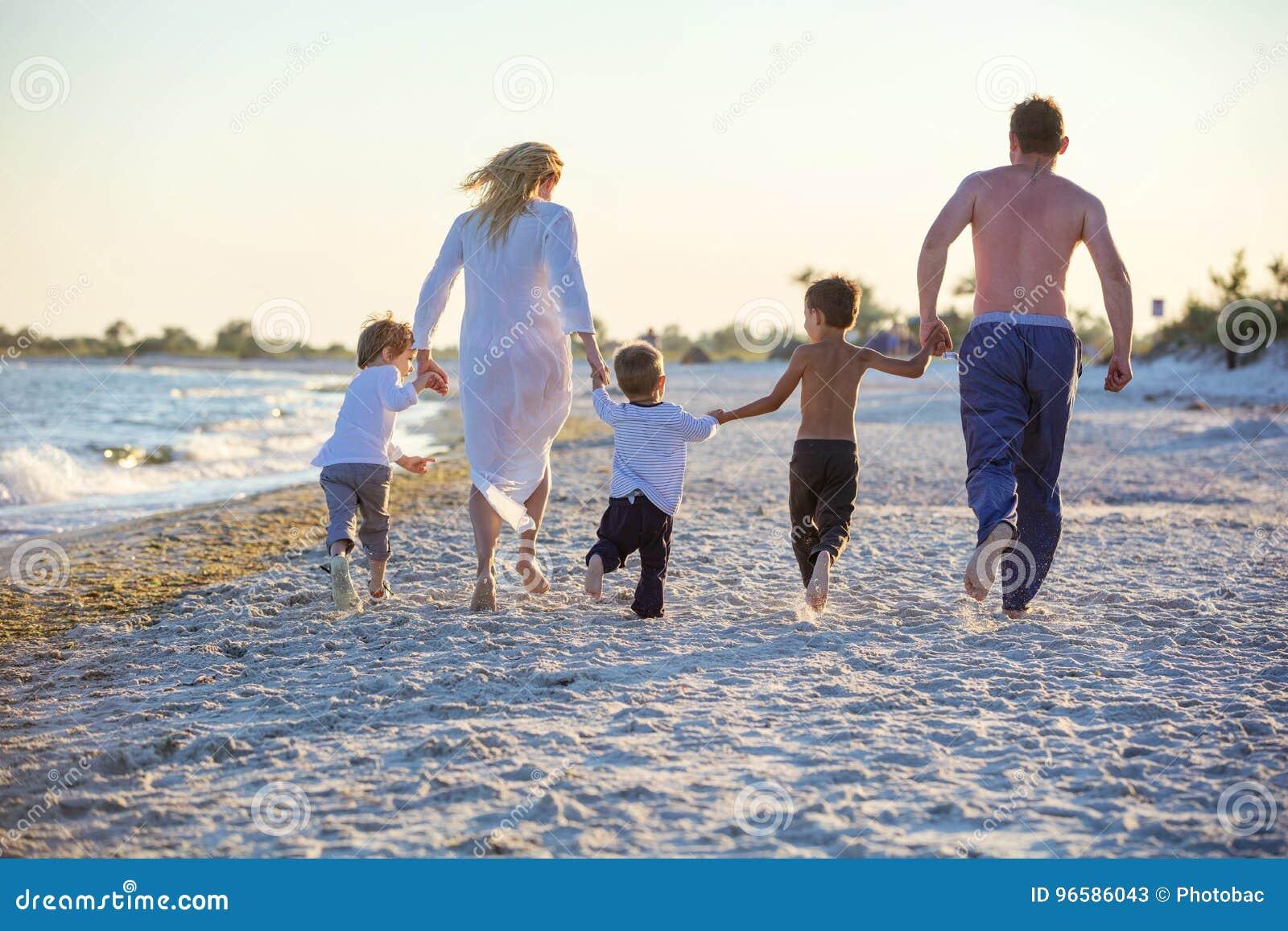 Familia joven feliz que corre en la playa antes de puesta del sol