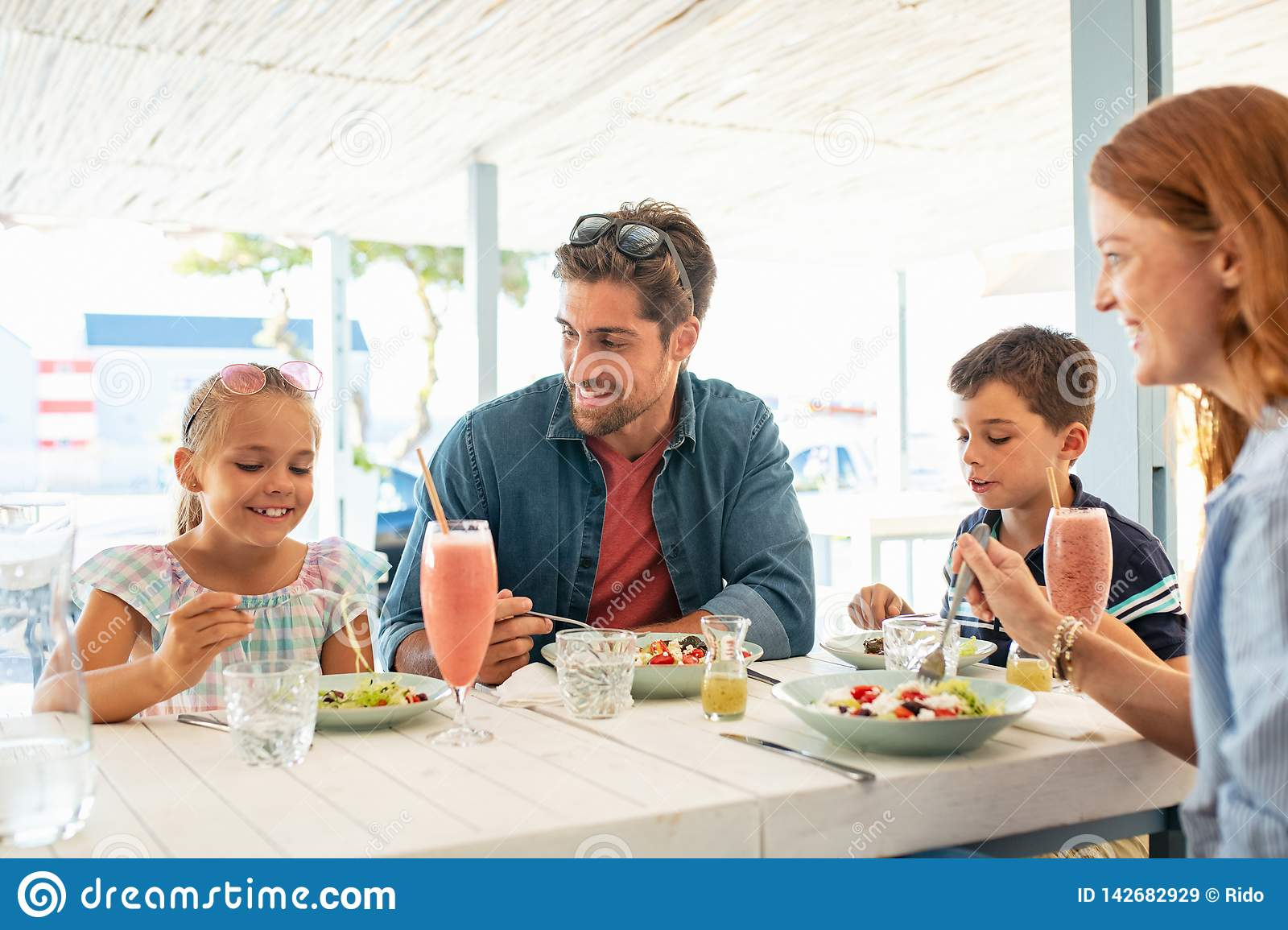 Familia joven feliz que disfruta del almuerzo al aire libre