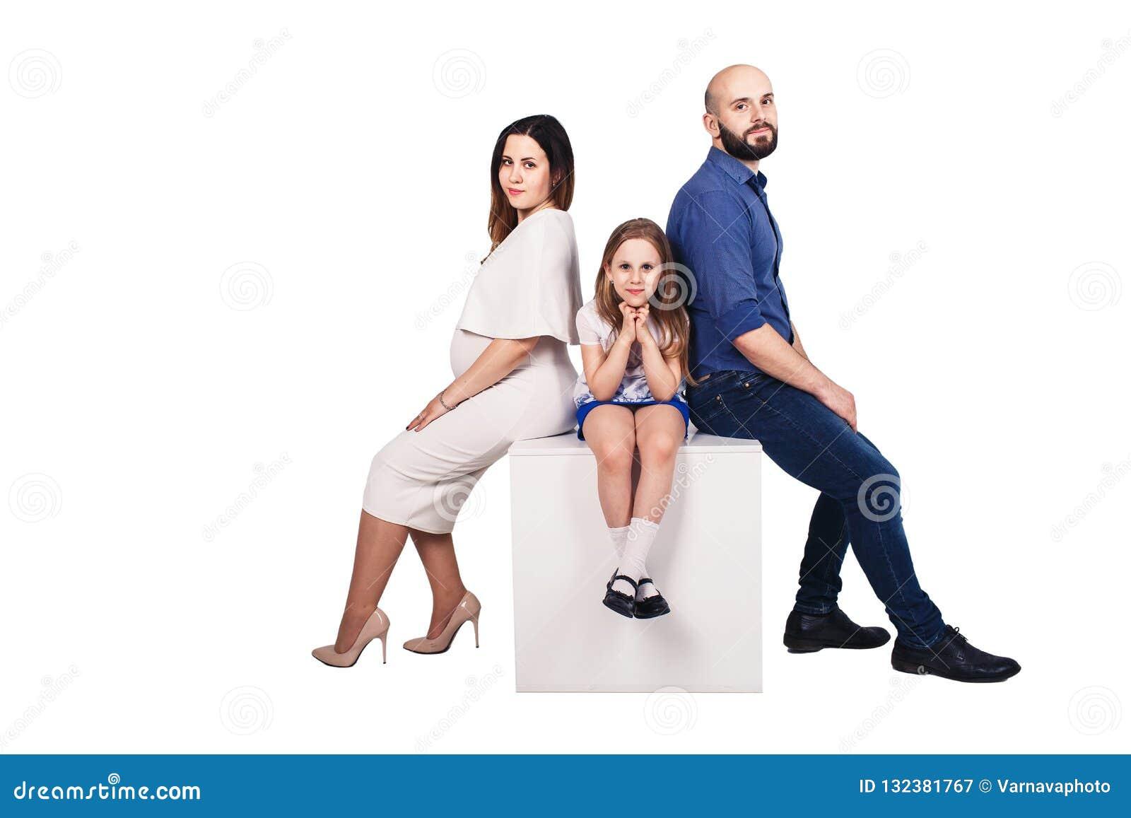 Familia joven feliz que se sienta en un pedestal contra el fondo blanco