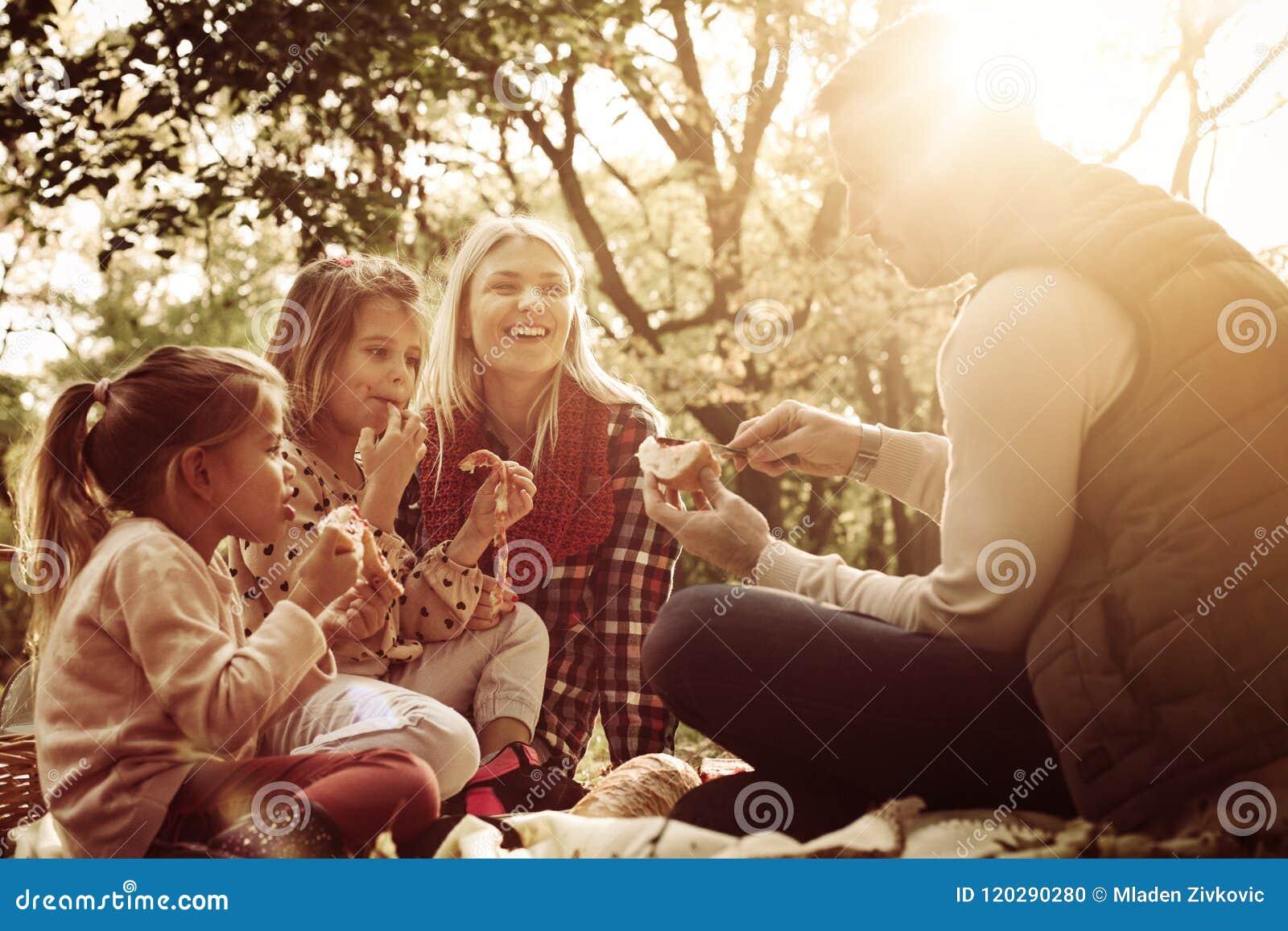 Familia joven feliz que tiene comida campestre junto en parque