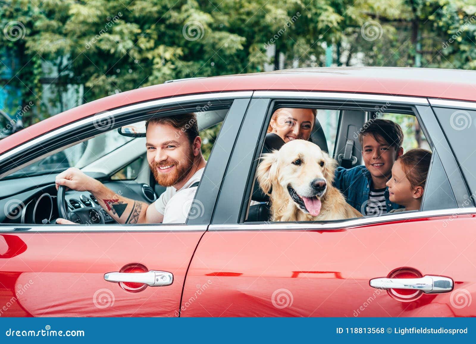 Familia joven hermosa que viaja en coche