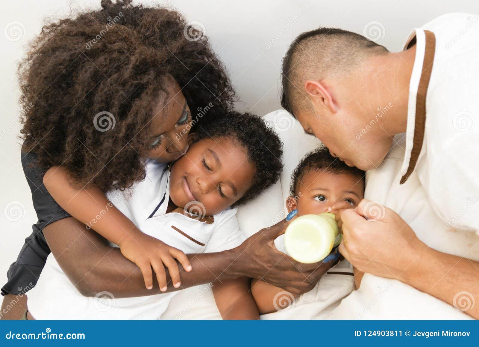 Familia joven Padres que alimentan a un niño infantil con leche Multi y