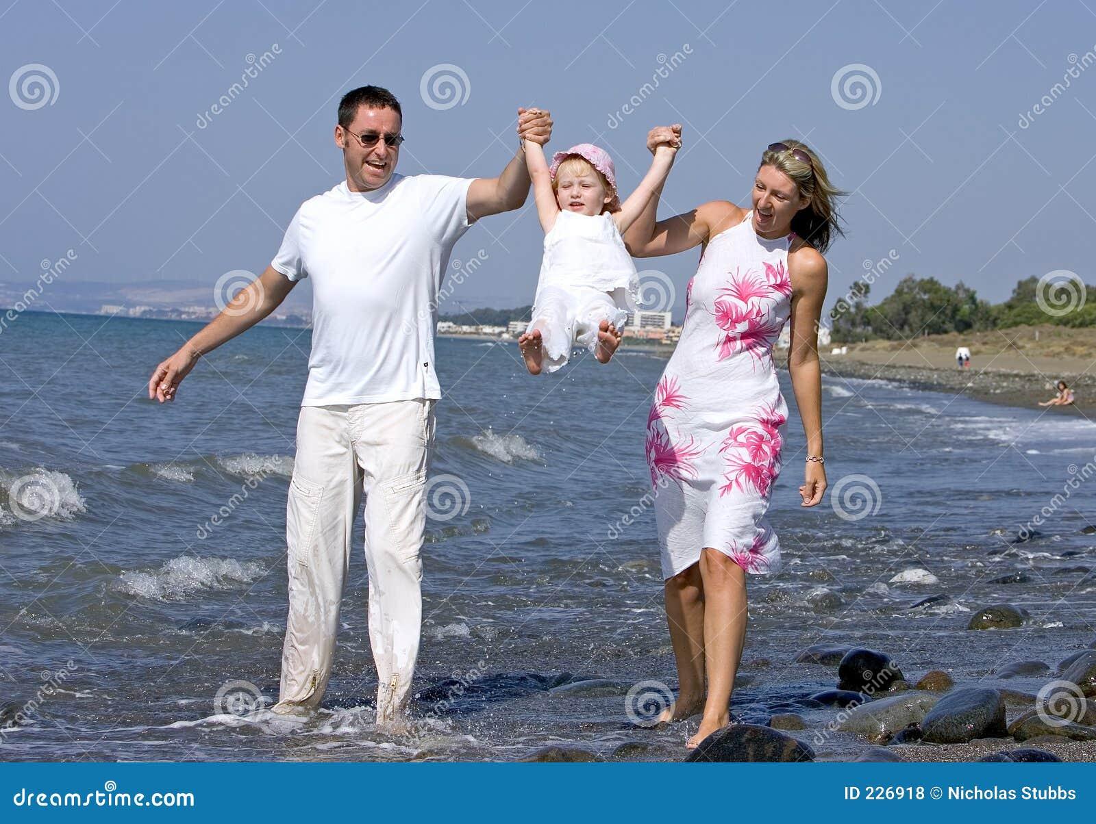 Familia joven que juega con la hija en la playa en España